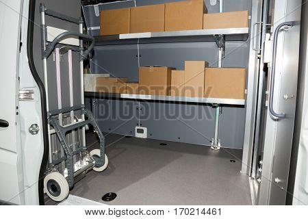 Packages and handtruck in a delivery truck.