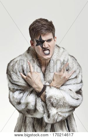 Portrait of frustrated young man in fur coat clenching teeth and making rebellious gesture against gray background