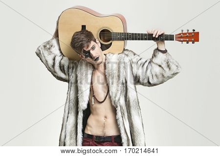 Portrait of young male guitarist in fur coat holding guitar over shoulder against gray background
