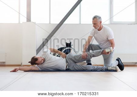 Stretching muscles. Serious athletic strong physical therapist stretching the handicapped and assisting while holding leg of the patient and expressing concentration