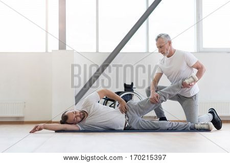 Morning routine of disabled people. Attentive helpful strong physical therapist stretching the handicapped and assisting while holding leg of the patient and expressing concentration