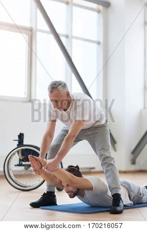 Working out with my disabled friend . Cheerful strong bearded orthopedist stretching the disabled and assisting while holding arms of the patient and expressing positivity