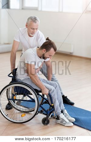 Taking care about my son. Active athletic bearded man helping his disabled son and assisting while holding the wheelchair and expressing positivity
