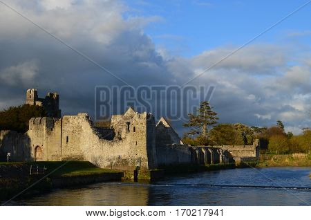 Desmond castle in Adare Ireland with river maigue running by it.