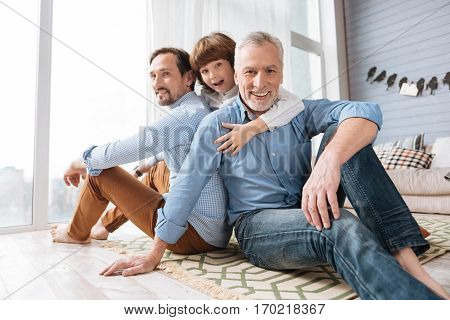 Male friendship. Handsome cheerful nice men sitting back to back on the floor and smiling while looking at you