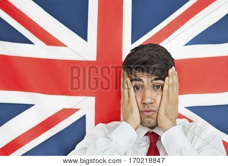 Portrait of a shocked Indian man with hands on cheeks against British flag