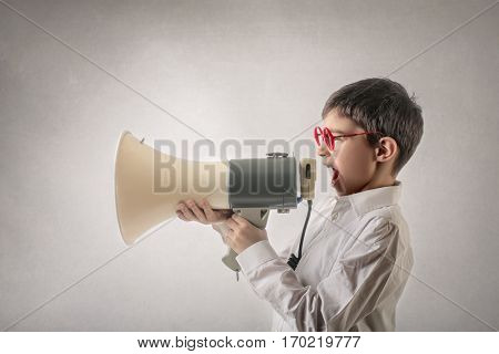 Boy with red glasses talking tinto huge megaphone