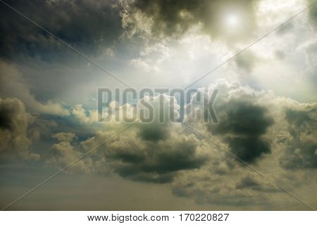 Overcast dark sky and the sun behind cumulus clouds.