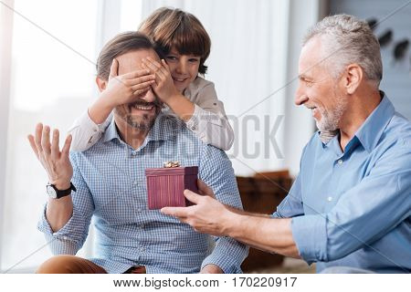 Pleasant surprise. Cheerful nice aged man holding a present box and looking at his son while presenting him with a gift