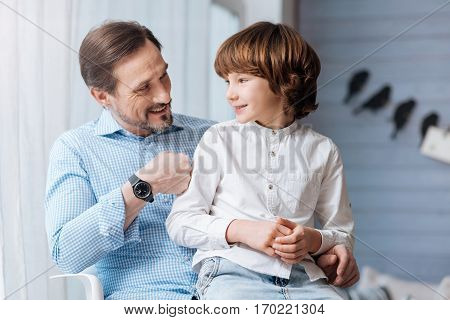 Spending time together. Delighted nice pleasant man sitting with his son and looking at him while having a great time with him