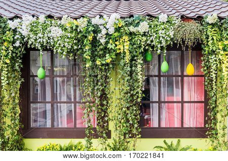 window decorated with colorful flowers and plants for Easter