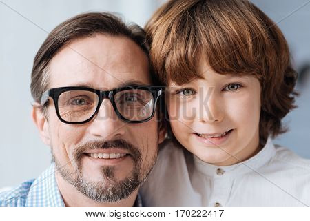 Two generations. Happy delighted father and son smiling and looking at you while standing together