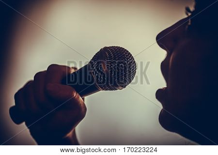 Close up image of a silhouette of a woman singing to a microphone.