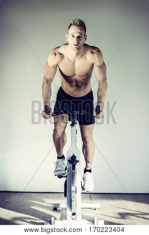 Attractive young man exercising in gym, spinning on stationary bike