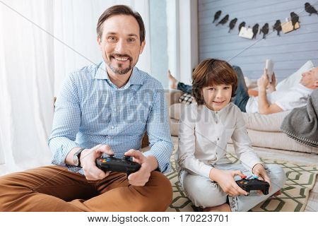 Enjoying themselves. Happy positive bearded man sitting cross legged on the floor and using a game console while playing video games with his son