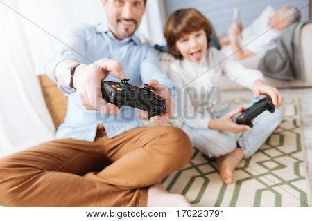 Modern electronic device. Modern small video game console being in hands of a positive handsome nice man while playing with his son