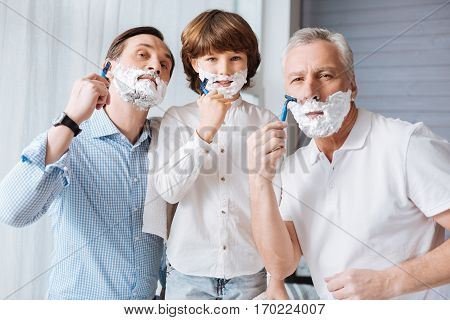 Time with family. Nice delighted positive men holding razors and shaving while having fun together
