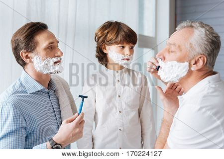 Time for shaving. Pleasant nice aged man holding a razor and shaving while concentrating on the activity