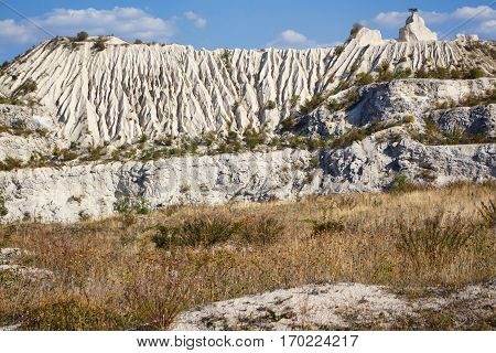 View on hills and fields from a limestone cliff at a quarry under a beautiful blue sky, abandoned white stone career, tree growing on stone, in fetesti village, Moldova