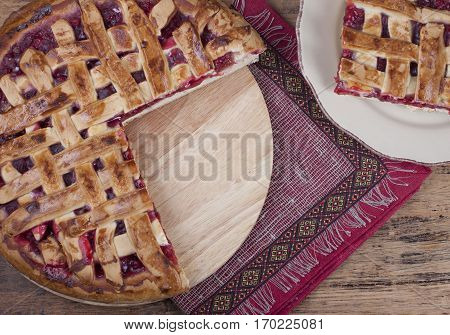 Pie of shortcrust pastry with red currants on a wooden board