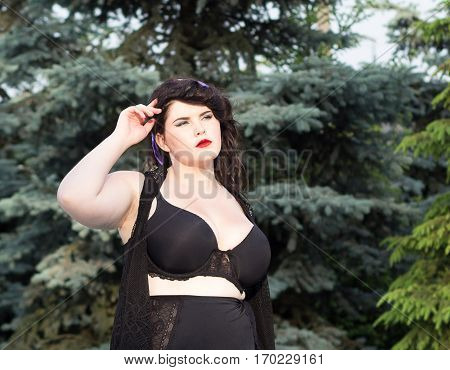 Young beautiful busty curvy plus size model with big breast in black bra outdoors