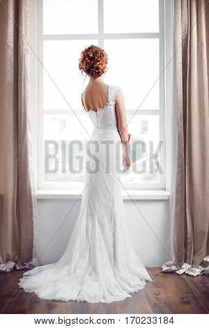 Wedding. Beautiful bride indoors against big window in full lenght back view