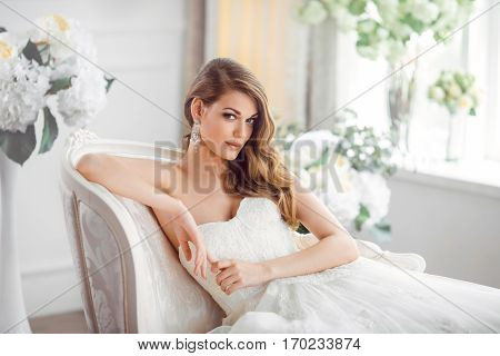 Wedding. Bride in beautiful dress sitting on sofa indoors in white studio interior like at home. Trendy wedding style shot. Young attractive caucasian brunette model like a bride against big window tender posing.