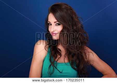Coquette Grimacing Emotional Makeup Woman With Long Curly Hair Style Looking On Blue Background