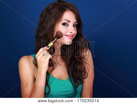 Beautiful Makeup Woman Applying Make-up Powder By The Brush On Clean Skin Face On Blue Background. C