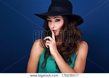 Beautiful Makeup Female Model In Hat Showing Secret Sign On Blue Background With Empty Copy Space. C