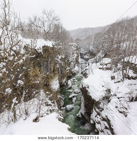 Green swirling cold water of the Belaya river in the narrow stone gorge hadzhohskaya tasnina gorge on the outskirts of the village Kamennomostsky (Adygea) on the coldest winter day