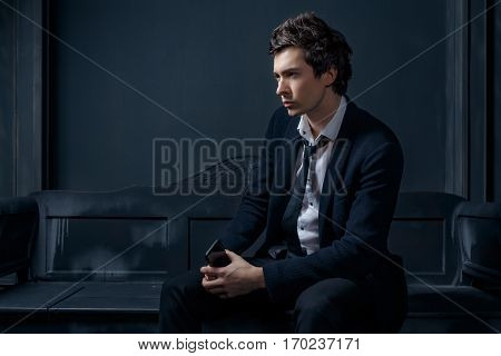 Man in the black suit in dark room. Dark room in loft style.