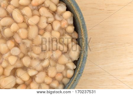 Top close view of a serving of organic navy beans in an old stoneware bowl atop a wood table.