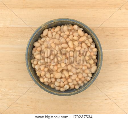 Top view of a serving of organic navy beans in an old stoneware bowl atop a wood table.