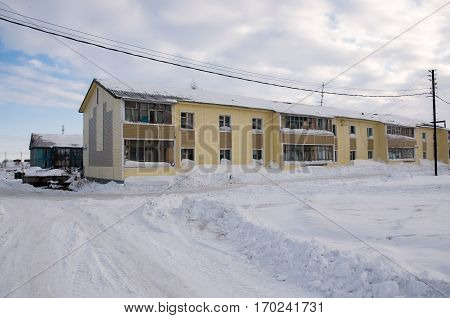 Old two-storied  yellow house in winter field with snow, North