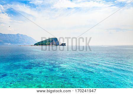 Seascape with desert island in blue heavens.