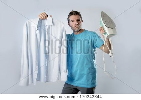 young attractive and satisfied man holding iron and slick shirt smiling happy and proud in male ironing good style and domestic work concept isolated even background