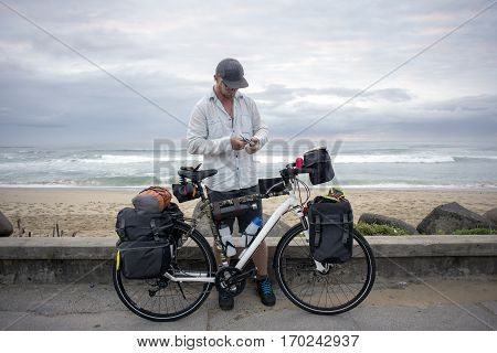 Long Distance Cyclist With Bicycle By Ocean