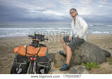 An adventure cyclists sits on a rock by the beach and ocean with his packed bicycle standing next to him.