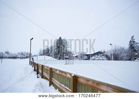 An outdoor ice skating rink and a hockey net with tall frost covered trees in the background in a winter landscape