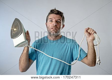 young crazy desperate and frustrated man doing housework holding iron and cable stressed and confused in unskilled and unable male for ironing isolated on even background