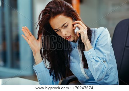 Bad mood businesswoman on the phone at the office