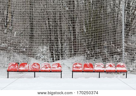 A number of red seats at a stadium in the snow, in the profile have the same number of seats in the blue snow. Images can be used in tandem. In the background netting