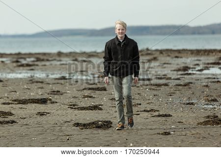 Single Blond Boy Walking On Beach Outside