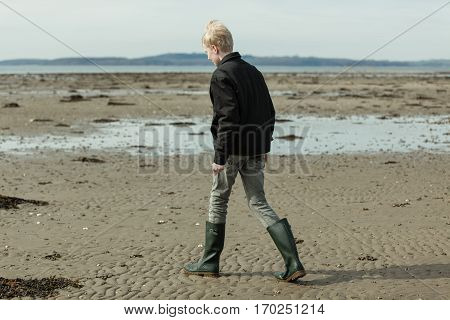 Boy In Tall Boots And Jacket Walking On Beach
