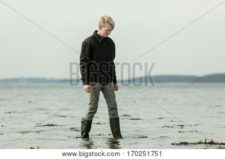 Teen Youth Stepping In Water During High Tide