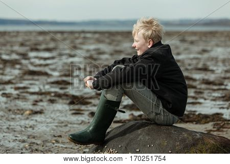 Happy Teen Boy In Boots Waiting For The Tide