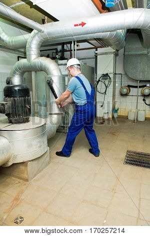 technician turns the valve in the technical room