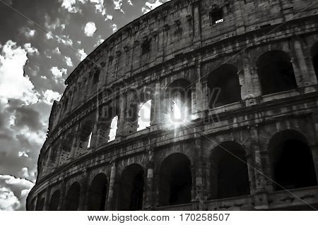 Artistic sun through the Colosseum black and white