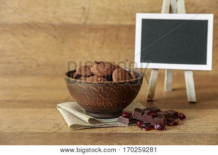 Natural chocolate cookies with cranberries and hazelnuts in the bowl near chocolate, cranberries and blackboard on wooden background in rustic style. Horizontal.